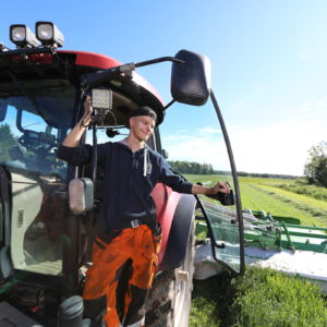 Maanviljelijä seisoo traktosin ovella ja katselee peltomaisemaa.