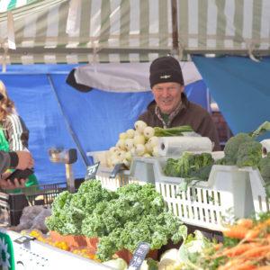 Kuva vihanneskojusta jossa on myynnissä lehtikaalia, parsakaalia ja kevätsipulia.