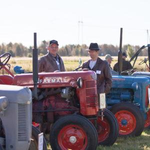 Kaksi miestä seisoskelee traktori-näyttelyssä ja keskustelee traktoreista.